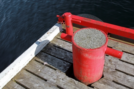 bollards: Red mooring bollards on wooden pier