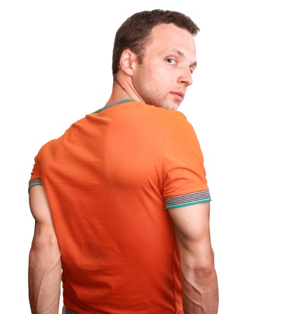 Muscular young man in orange t-shirt turns isolated on white background photo
