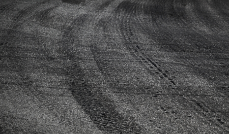 squeal: Dangerous turn. Abstract road background with tires tracks on asphalt