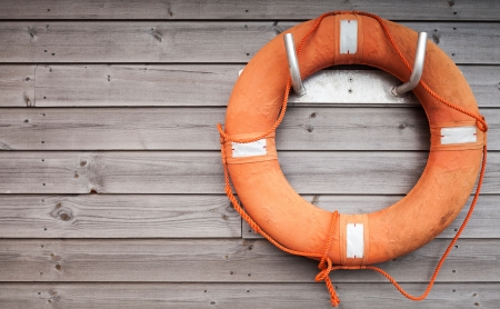 life preserver: Red lifebuoy with rope on weathered wooden wall in port