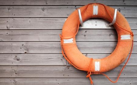 Salvavidas rojo con la cuerda en la pared de madera resistido en el puerto Foto de archivo
