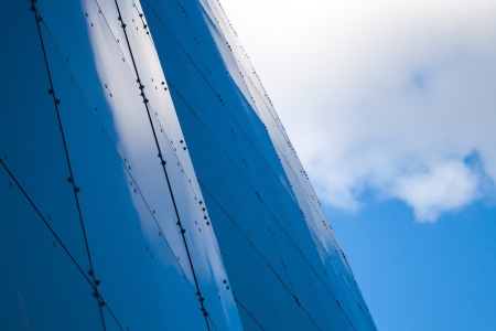 Modern abstract architecture background with steel wall panels reflect blue cloudy sky photo