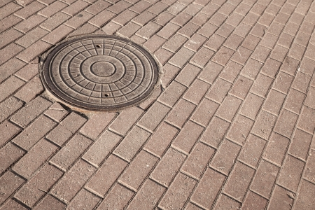 Round steel sewer manhole on the cobblestone pavement photo