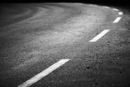 Draaien asfaltweg met markering lijnen en bandensporen Close up foto met selectieve aandacht
