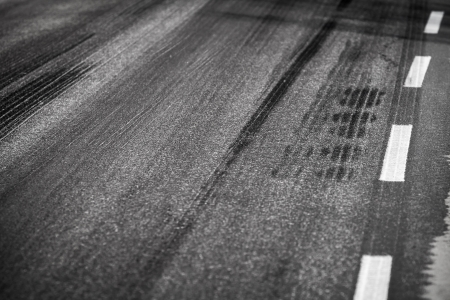 Asphalt road with marking lines and tire tracks  Close up photo with selective focus photo