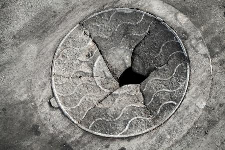 Old broken manhole cover on the asphalt road photo