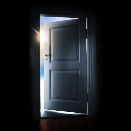 cielos abiertos: Abriendo la puerta azul en un cuarto oscuro con luz brillante y el cielo fuera Foto de archivo