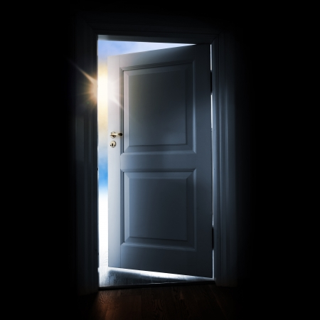 Opening blue door in a dark room with shining light and sky outside photo