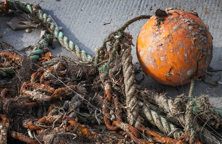 Old tangled fishing nets with orange sphere buoy lies on the seacoast photo