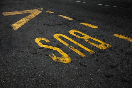 Yellow bus stop marking on urban asphalt road photo