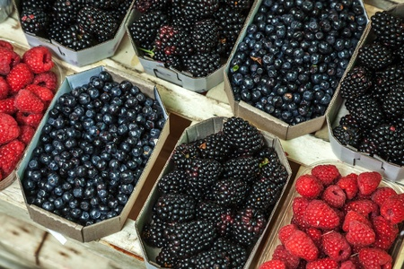 Different berries lay on the counter in paper boxes photo