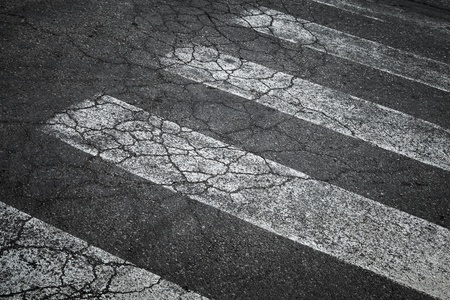 Pedestrian crossing marking on old damaged asphalt road photo