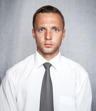 Young serious man in white shirt with tie over gray background  Studio portrait Stock Photo
