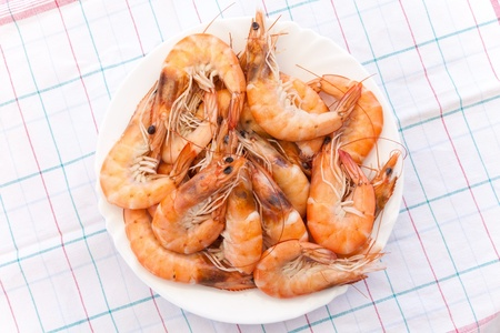 Pile of prepared shrimps lays on round white plate photo