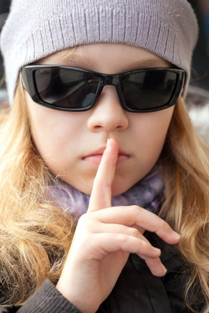 Little girl in sunglasses shows silence sign photo