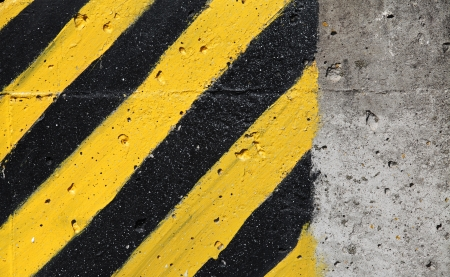 Black and yellow striped caution sign on gray concrete wall photo