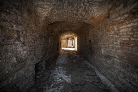 Old stone fortress dark stone tunnel perspective with glowing end photo