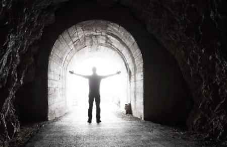 トンネル: 白熱端で暗いトンネルに立っている男