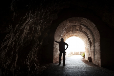 Young man stands relaxed in dark tunnel and looks in the light photo