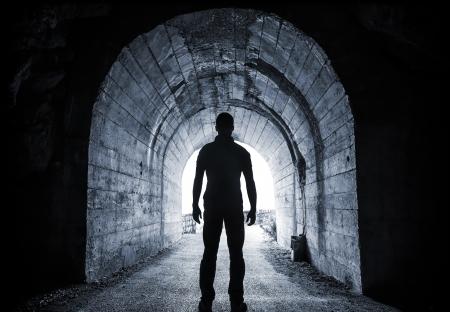 젊은 남자가 어두운 터널의 약자와 빛나는 끝에서 찾습니다 스톡 콘텐츠