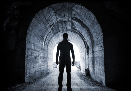 escape: Young man stands in dark tunnel and looks in the glowing end