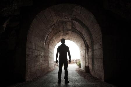 tunnel di luce: Giovane uomo si trova nel tunnel buio e guarda fuori alla fine incandescente Archivio Fotografico