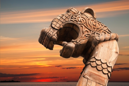 Carved wooden dragon on the bow of Viking ship above evening cloudy sky photo