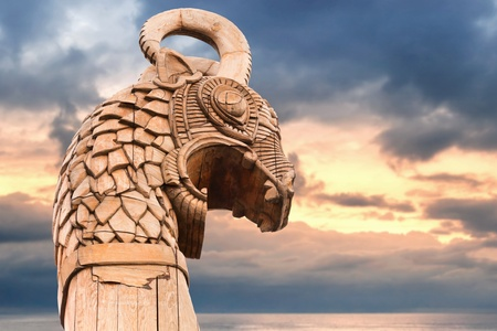 Carved wooden dragon on the bow of Viking ship above morning sky and sea photo