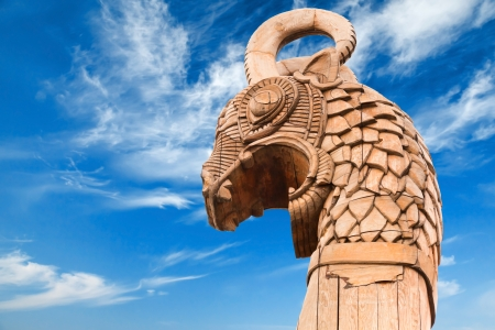 celts: Carved wooden dragon on forepart of the ancient Viking ship above dramatic blue sky