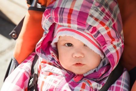 Little baby girl in warm outwear seats in pram on the walk photo
