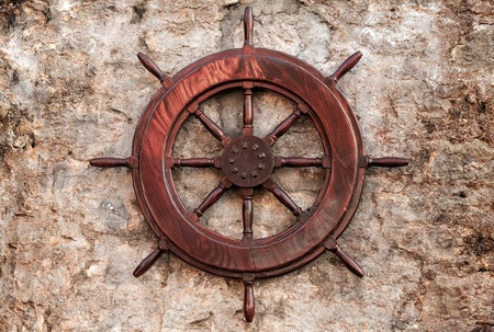 Old wooden ship steering wheel on stone wall photo