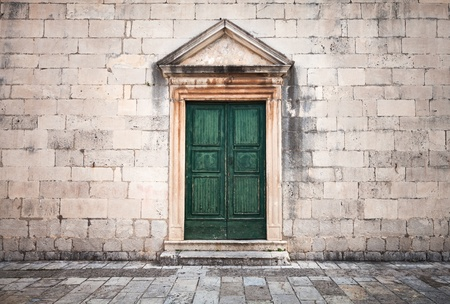 Stone wall with green wooden door and pavement of vintage town square Stock Photo - 21780769