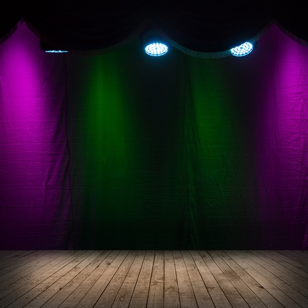 Dark scene interior with spotlights, wooden stage and colorful background photo