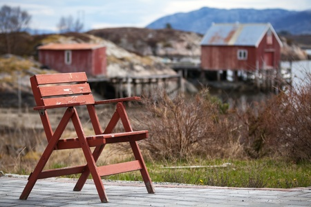 Red wooden chair in small Norwegian  village on the sea coast photo