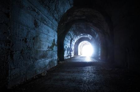 暗い放棄されたトンネルから青い白熱出口