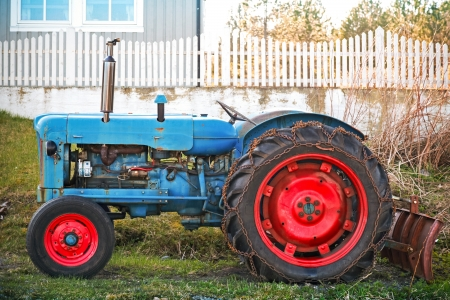 Small old blue tractor with red wheels stands on grass nearby wooden fence in Norway photo