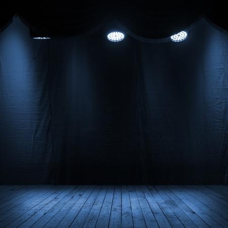 Donkerblauw interieur scene met spots, houten podium en stof achtergrond