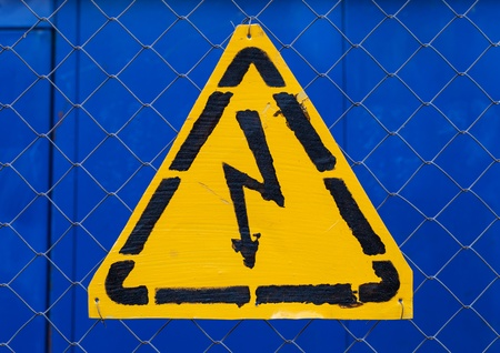 High voltage yellow sign mounted on blue metal rabitz grid photo