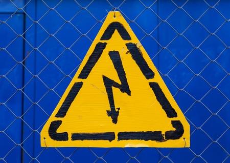 rabitz: High voltage yellow sign mounted on blue metal rabitz grid Stock Photo