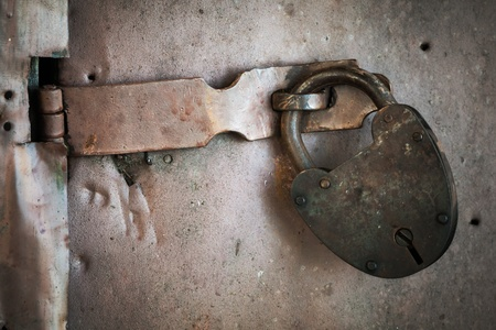 Old rusted lock hangs on metal door. Closeup photo photo