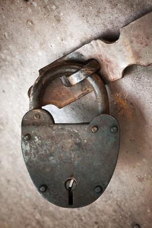 Old rusted lock hangs on metal door.  photo