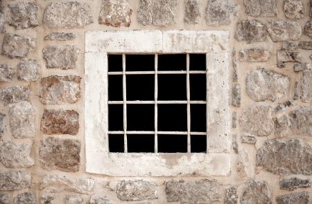 ancient prison: Ancient stone prison wall with metal window bars Stock Photo
