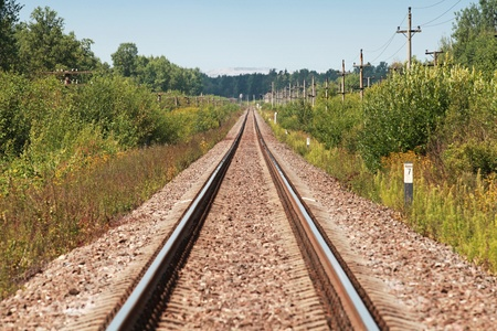 Long straight railway perspective with poles, green grass and blue sky photo