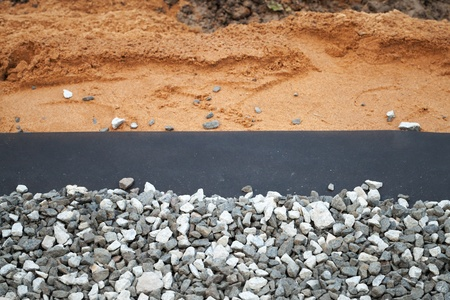 Geotextile with gray gravel above sandy backdrop photo