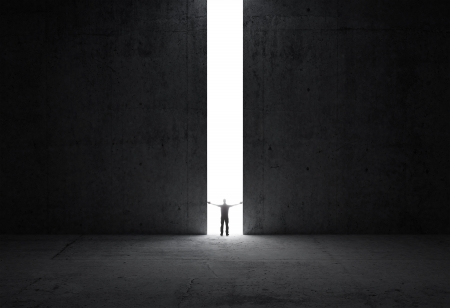 opening door: Dark abstract concrete interior  Man stands in the light of opening