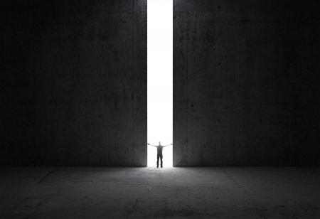 Dunkle abstrakten Beton Innenraum Mann steht im Licht der Öffnung