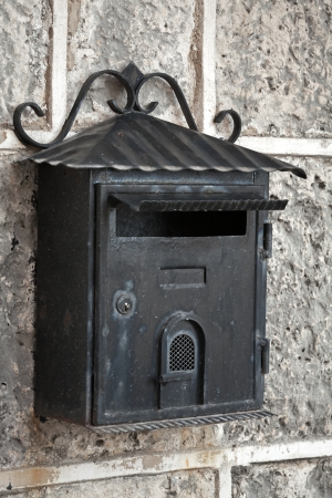 Old weathered black metal mailbox mounted on gray stone wall Stock Photo - 21913467