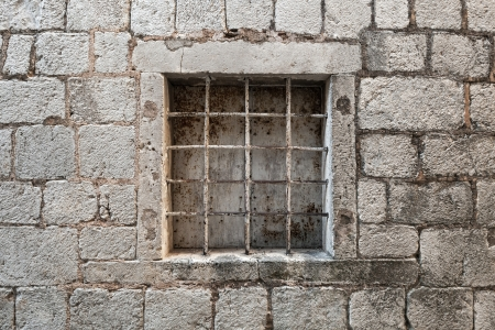 Locked ancient stone prison wall with metal window bars photo