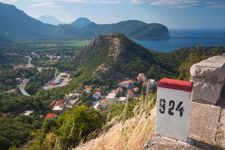 White and red kilometer stone post on the roadside in Montenegro photo