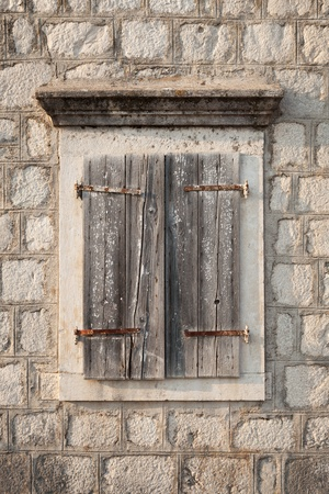 Ancient window with closed wooden jalousies in gray stone wall. Perast town, Montenegro photo